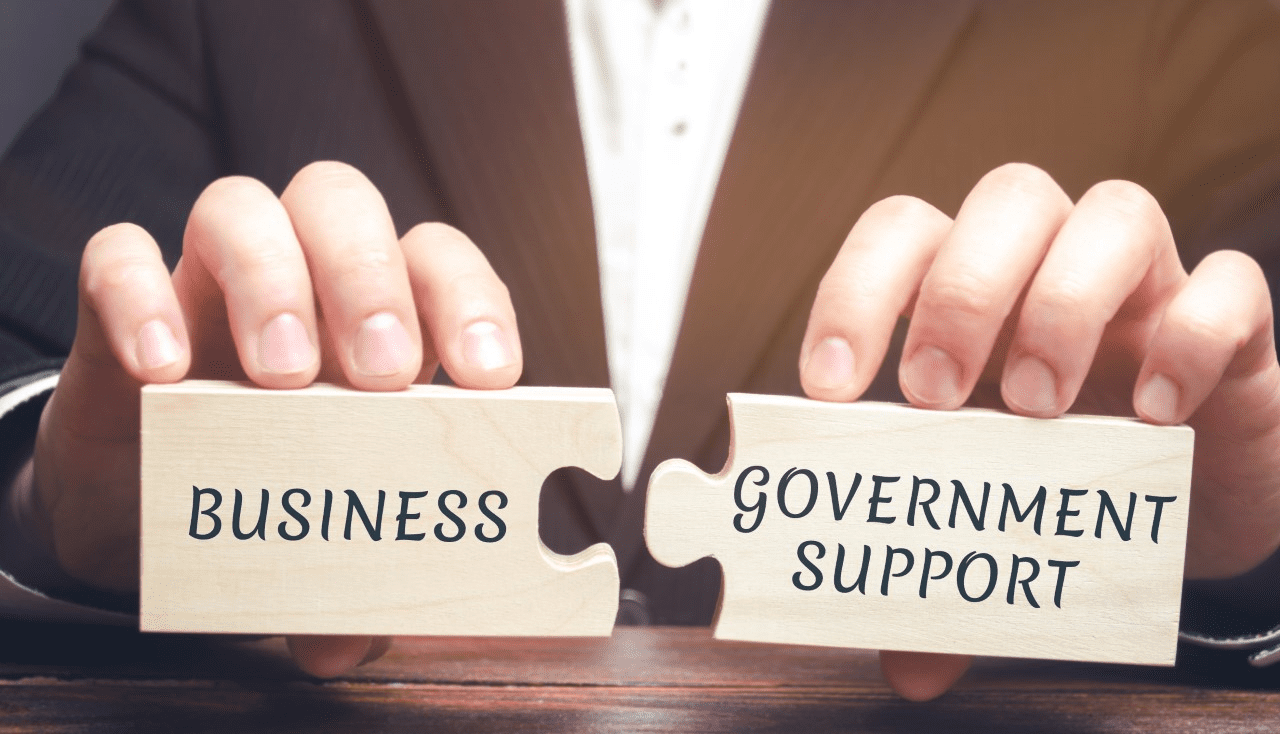 Two jigsaw pieces spelling 'business government support'