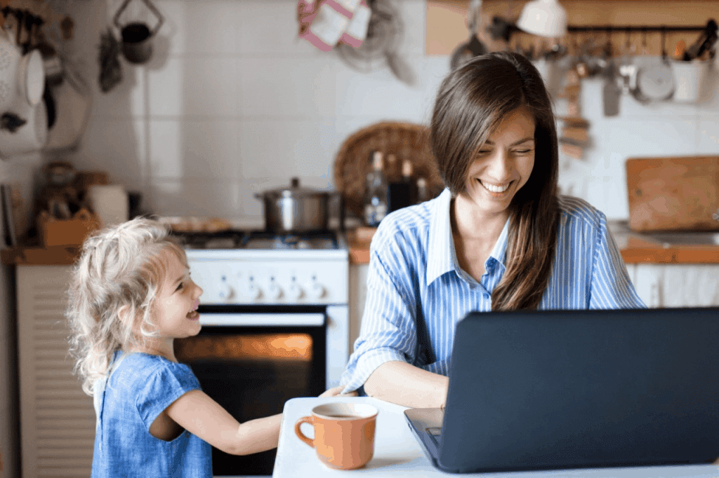 A mother working at her laptop whilst her daughter is pulling her sleeve